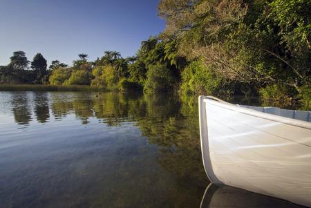 lake front: Front of small wooden row boat with reflections Lake Rotorua New Zealand Stock Photo