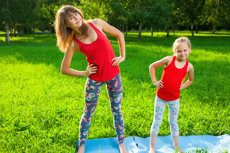 mum and daughter: Mother and her daughter outdoors doing yoga, healthy lifestyle Stock Photo