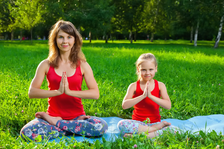 heathy: Mother and her daughter outdoors doing yoga, healthy lifestyle Stock Photo