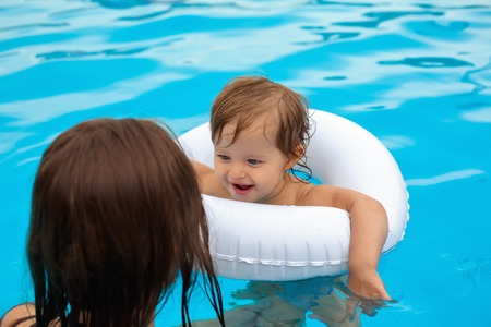 lifeline: Young mother with her little daughter in the pool, learning to swim Stock Photo