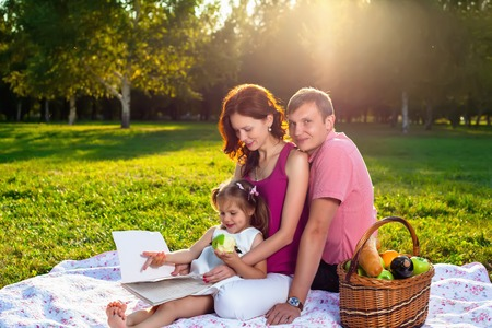 litle: Happy young family having picnic at meadow at summer day. Litle girl shows blank notebook