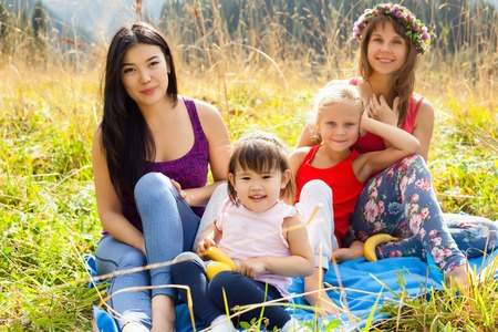 hapy: Asian woman with child along with his caucasian girlfriend and her daughter on a picnic in the mountains on a Sunny day