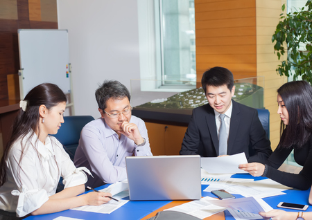 bussines people: Business meeting, Asian people sitting for a  table with business plan on high floor in the office. Asian nationality a woman  shows a business graph of his business partner. Stock Photo