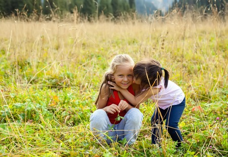 hapy: Little Asian girl walking with caucasian girl on meadow with mountains in the background, isses on the cheek