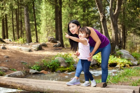 outumn: Asian Woman with her little daughter in the woods near the river standing on a log. posing smiling, litle baby indicated hand Stock Photo