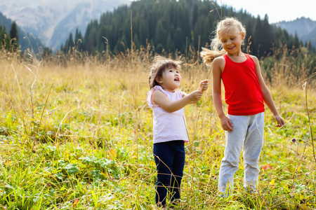 hapy: Little Asian girl walking with caucasian girl on meadow with mountains in the background