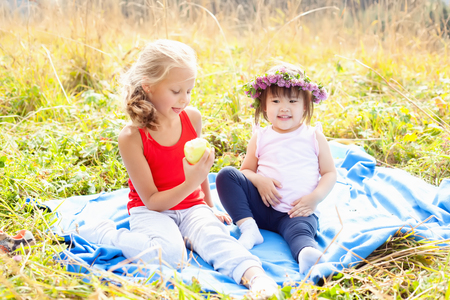 hapy: Asian child along with his caucasian girlfriend on a picnic in the mountains on a Sunny day Stock Photo