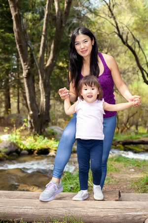 hapy: Asian Woman with her little daughter three years old in the woods near the river standing on a log. posing smiling
