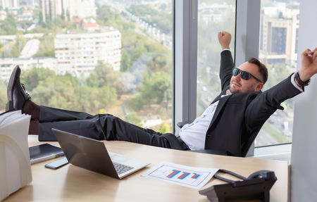 slacker: Businessman in suit working on laptop, at a table in the office, having a rest with leg on the table Stock Photo