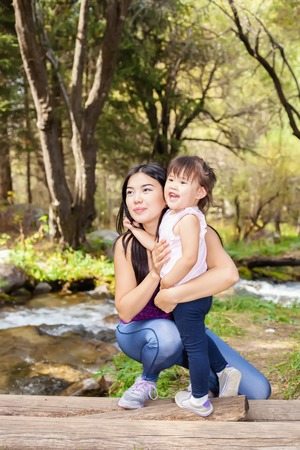 outumn: Asian Woman with her little daughter in the woods near the river standing on a log. posing smiling