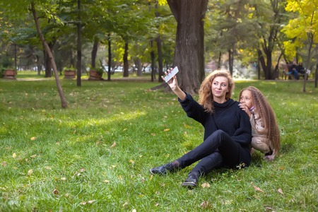 hapy: Mother with daughter seven years old in autumn Park at sunset. A woman makes a selfie together with his child Stock Photo