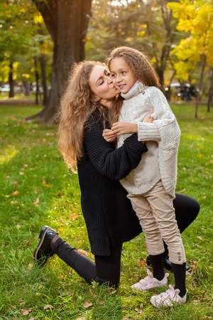 hapy: Mother with daughter seven years old in autumn Park at sunset. mom kisses her daughter