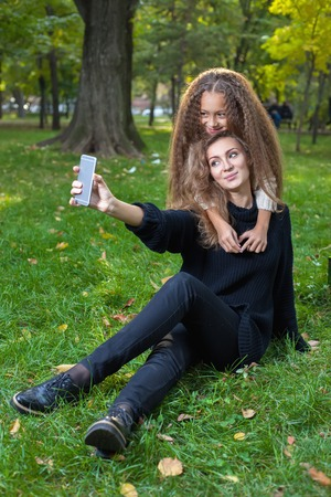 hapy: Mother with daughter seven years old in autumn Park at sunset. The daughter hugs her mom, a woman makes a selfie together with his child
