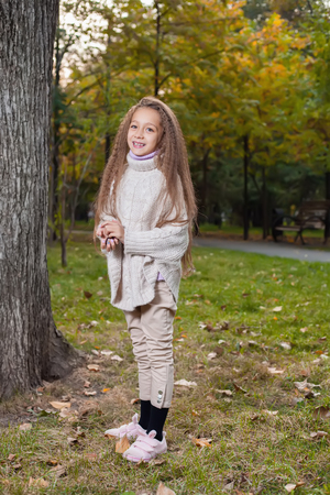 litle: Beautiful little girl in white sweater posing in autumn Park near the tree