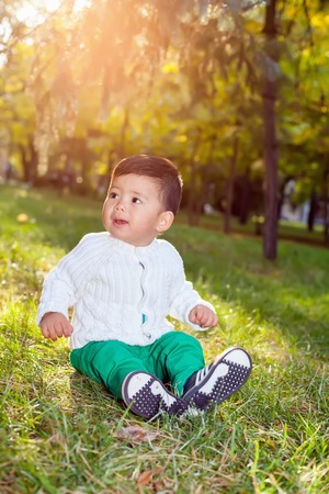 hapy: A small asian child plays in the Park sitting on the grass, posing smiling