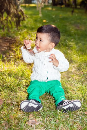 hapy: A small asian child plays in the Park sitting on the grass, posing smiling. Little child holds the sunglasses