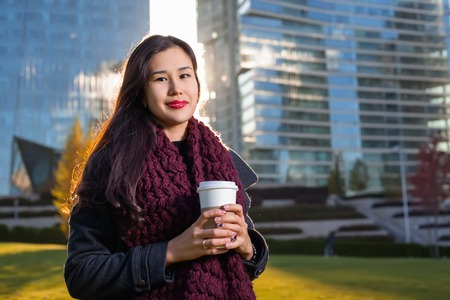 Asian woman holding coffee in hand, standing outdoors behind skyscraper in the sunlight. enjoying her morning coffee in the sunlight. Woman smaling happy in her 20s