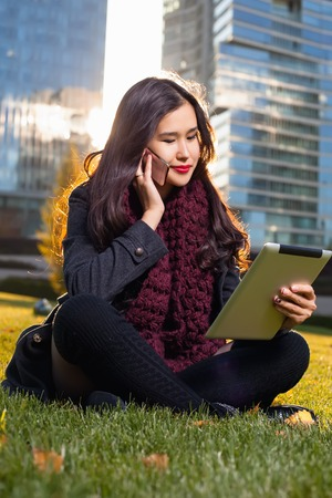 Asian woman holding tablet in hand, sitting outdoors behind the skyscrapers in the rays of the sun. Woman reading information, looking at tablet, talking on a cell phone Stock Photo