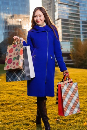 overspending: Asian woman holding shopping bags in hand, standing in outdoors over a skyscraper in sunlight. Walking on the grass posing smiling after shopping
