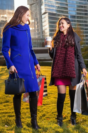 sopping: Two Asian woman holding shopping bags in hand, standing in outdoors over a skyscraper in sunlight. Walking on the grass posing smiling after shopping