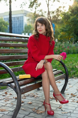 beuty of nature: young beautiful woman sitting on a bench in autumn Park at sunset. The girl in the red coat has a rest after a hard day Stock Photo
