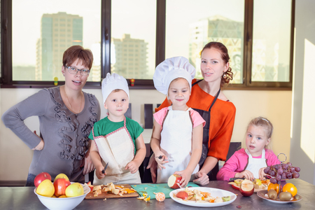 Three cute kids are preparing a fruit salad in the kitchen. Healthy eating Banco de Imagens