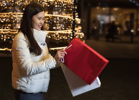 Young Asian woman posing against the backdrop of a Christmas tree with garlands to night. After shopping, holding gifts
