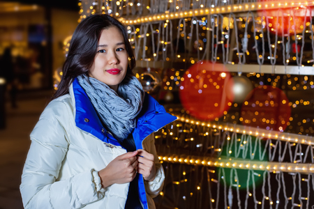 back alley: Young Asian woman posing against the backdrop of a Christmas tree with garlands to night. Outdoor Christmas decoration, lit alley.