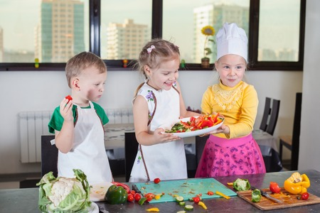 Three cute kids are preparing a salad in the kitchen. Healthy eating