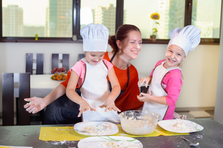Two lovely children together with mother preparing a cake of dough in the kitchen. Healthy eating