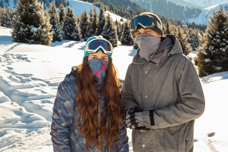 Couple snowboarder in place in the mountains. Mountains in the background