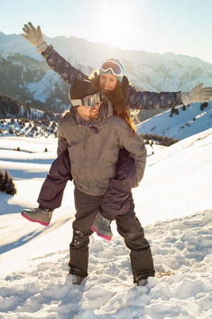Smiling snowboarder holding girlfriend on his back. Mountains in the background