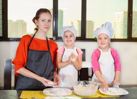 Lovely children together with mother preparing a cake of dough in the kitchen. Healthy eating Banco de Imagens
