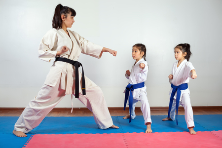 Coach woman showing martial art for children. Fighting position, active lifestyle, expressing emotions Stock Photo