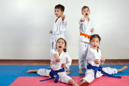 Four children demonstrate martial arts working together. Fighting position, active lifestyle, expressing emotions Stock Photo