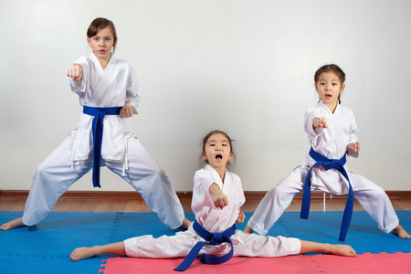 Three little girls demonstrate martial arts working together. Fighting position, active lifestyle, practicing fighting techniques
