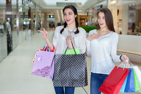 Two cute girl walks in mall with gift bags. Pointing at the boutique. After shopping. Shopping
