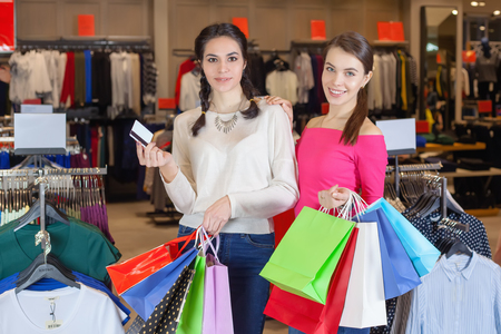 Two beautiful girls make themselves at the mall with a bag of gifts. Holding a credit card in her hand for payment.