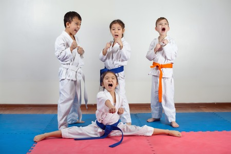 Four children demonstrate martial arts working together. Fighting position, active lifestyle, practicing fighting techniques
