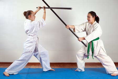 Two girls demonstrate martial arts working together. Fighting position, active lifestyle, practicing fighting techniques Stock Photo