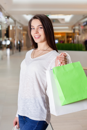 Beautiful girl walks in the mall with gift bags