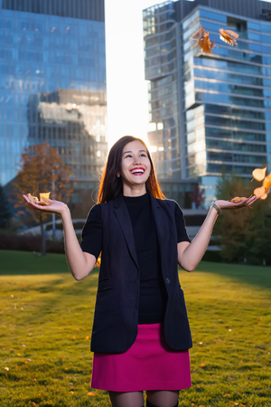 The girl catches the leaves of the trees. on the background of skyscrapers in sunlight