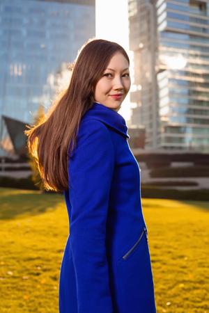 Girl walks on the grass. in the background skyscraper in sunlight