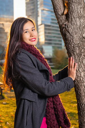 Smiling girl posing near the tree. On the background of skyscrapers in sunlight