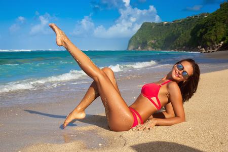 Cute girl in red bikini walking at tropical beach bali. Posing lying on the sand
