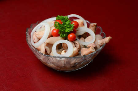 Mushrooms belong to a plate on the table. They are decorated with parsley, tomatoes and onions.; Stock Photo