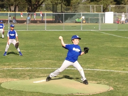 Boy pitching in little league baseball game.