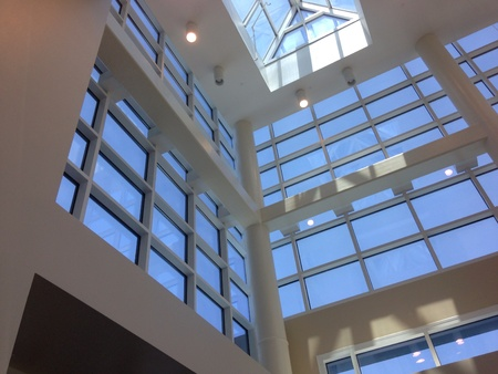 view of an atrium in a building: Upward view from inside of commercial building.
