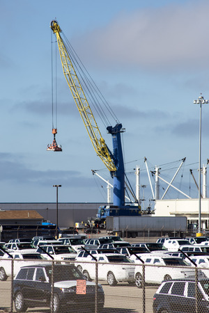 unloading: A big blue crane is unloading cargo containers from a cargo ship