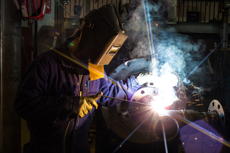 A skilled welder is making a weld on a pipe joint